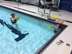 A teacher swims with her student